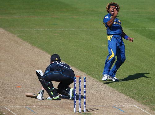 Lasith Malinga (R) of Sri Lanka celebrates bowling Brendon McCullum