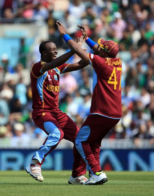 Kemar Roach celebrates after picking a wicket