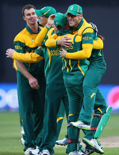 AB de Villiers the captain of South Africa lifts Faf Du Plessis (R) off his feet after catching Kamran Akmal of Pakistan