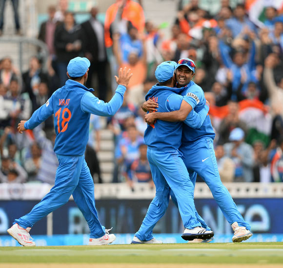 Ravichandran Ashwin (right) celebrates with team-mates after taking the catch to dismiss Chris Gayle