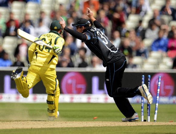 Australia's Phillip Hughes is run out by New Zealand's Martin Guptill (right)