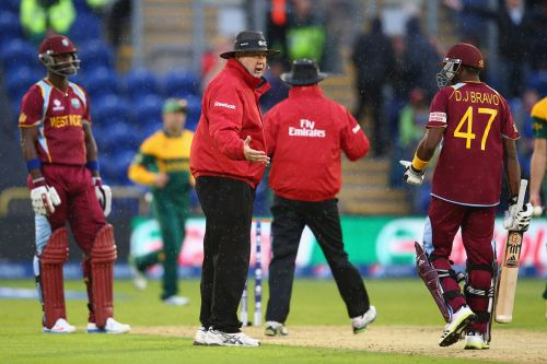 Umpire Steve Davis (2L) stops play as rain arrives as Dwayne Bravo (R) and Darren Sammy (L) of West Indies have to accept that South Africa go through to the semi-final as the match is tied on the Duckworth/Lewis method