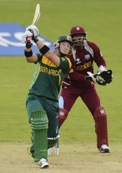 South Africa's Colin Ingram (L) hits a six as West Indies' Johnson Charles looks on