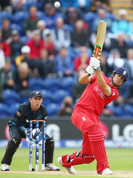 Alastair Cook (right) of England hits to the off side as Luke Ronchi (left) of New Zealand looks on