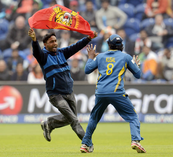 A Sri Lankan protester runs towards Kushal Perera
