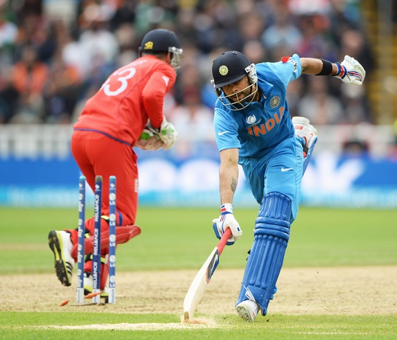 Virat Kohli of India stretches to make his ground