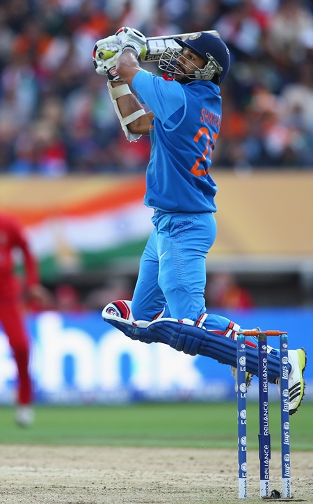 Shikhar Dhawan of India hits a six over backward point off the bowling of Stuart Broad