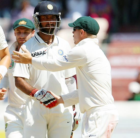 David Warner congratulates Cheteshwar Pujara as he walks back to the pavilion