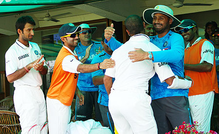 Shikhar Dhawan (right) is congratulated by teammates in the dressing room after scoring a century on debut on Saturday