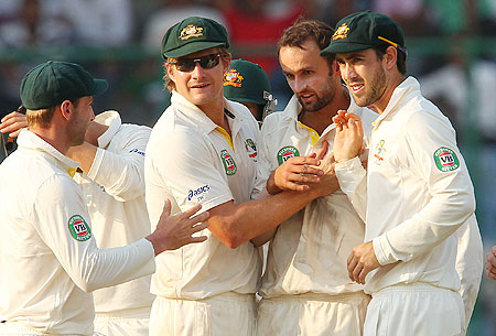 Nathan Lyon celebrates a wicket with teammates