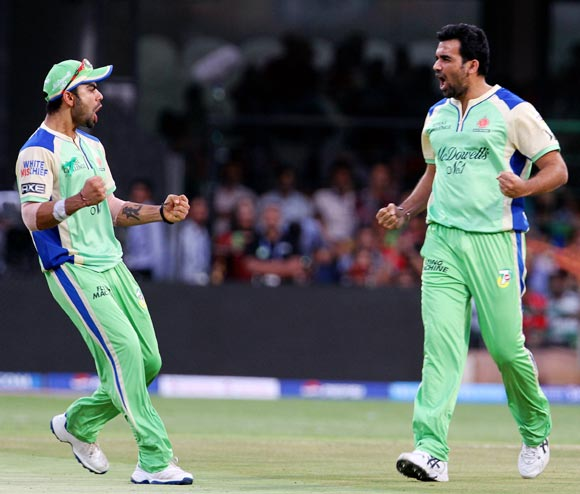 Zaheer Khan (right) celebrates with Virat Kohli after getting the wicket of Shaun Marsh