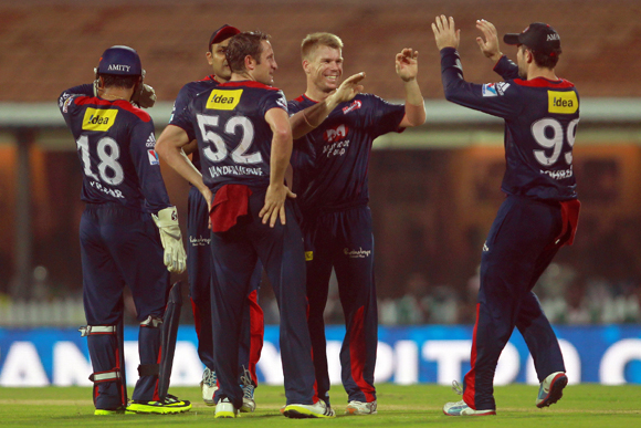 David Warner is congratulated by his teammates after taking a catch to dismiss Suresh Raina