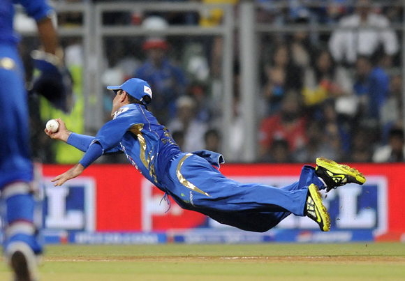 Ponting dives to his right to catch Unmukt Chand
