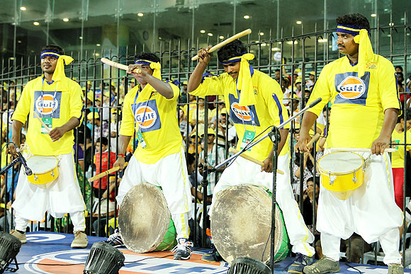 Performers go drumming during an IPL match
