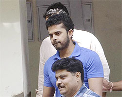 Former test bowler Shanthakumaran Sreesanth is taken to a court by police personnel in New Delhi