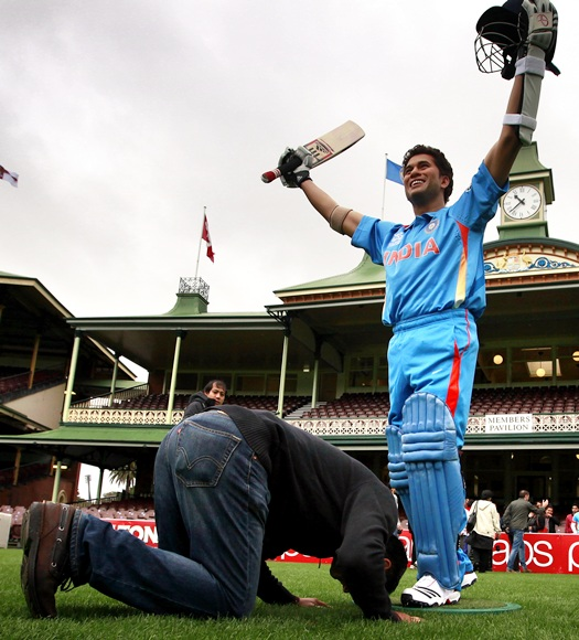 An Indian cricket supporter kneels in front of a wax figure of Indian cricketer Sachin Tendulkar
