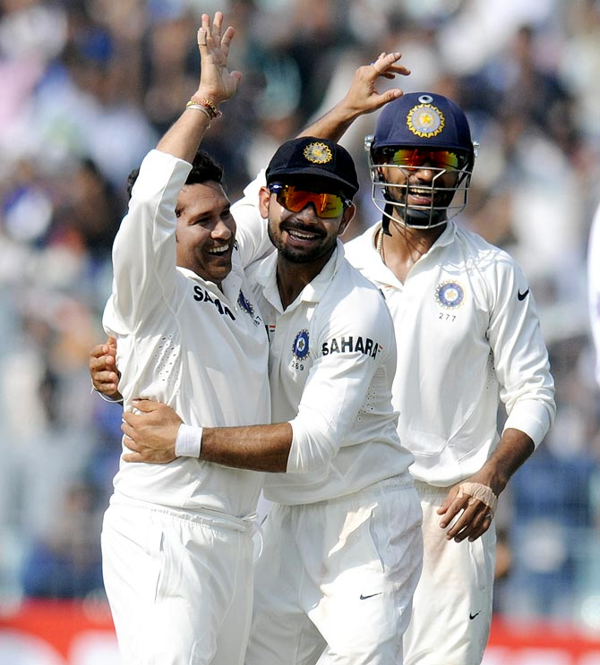 Sachin Tendulkar celebrates with the team mates after taking the wicket of Shane Shillingford