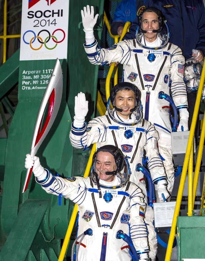 Expedition 38 Soyuz Commander Mikhail Tyurin of Roscosmos, holding the Olympic torch, Flight Engineer Koichi Wakata of the Japan Aerospace Exploration Agency, and, Flight Engineer Rick Mastracchio of NASA (top), wave farewell prior to boarding the Soyuz TMA-11M rocket for launch