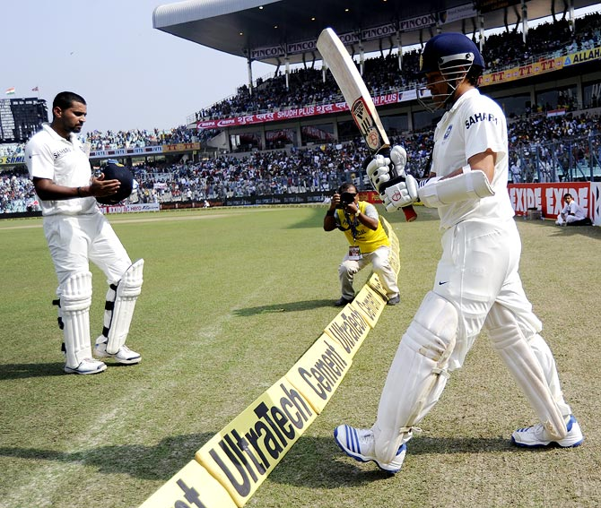 Sachin Tendulkar walks out to bat as Murali Vijay heads to the pavilion after his dismissal