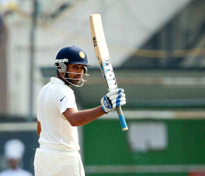Rohit Sharma raises his bat after completing his fifty