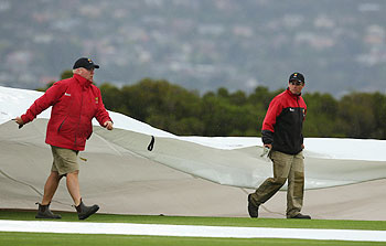 Groundstaff cover the pitch at the Bellrive Oval on Friday