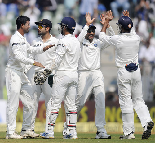 Pragyan Ojha is congratulated by teammates after picking his fifth wicket