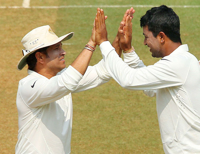 Pragyan Ojha of India celebrates the wicket of Kieran Powell of West Indies with Sachin Tendulkar