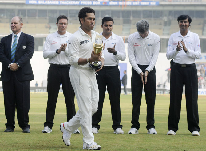 Sachin Tendulkar of India walks back with the trophy during a felicitation before the start of play on day one