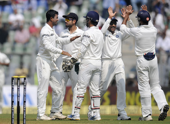 Pragyan Ojha of India celebrates the wicket of Kieran Powell