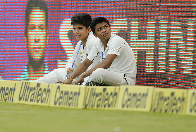 Arjun Tendulkar (left) does ball boy duty during Day 2 of the Test match at the Wankhede in Mumbai on Friday