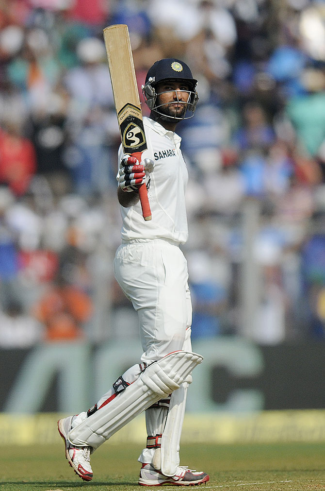Cheteshwar Pujara of India raises his bat after scoring a half century on Friday