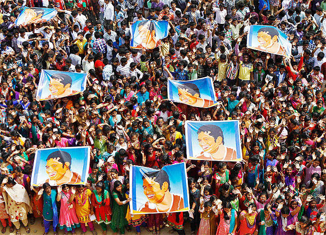 School children wave as they hold posters of Sachin Tendulkar at an event to honour him inside a school in Chennai