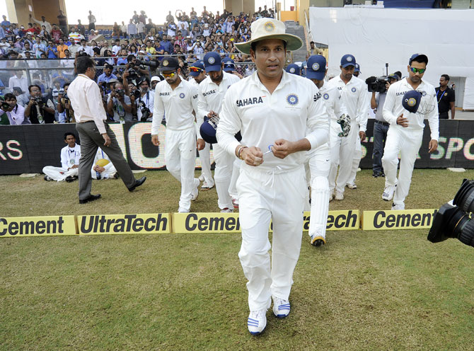 Sachin Tendulkar of India leads Team India to the middle at they walk to field during day three