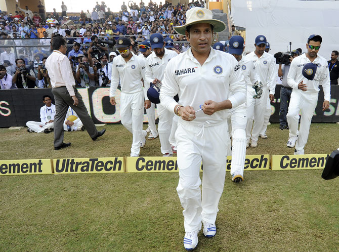 Sachin Tendulkar of India and Mahendra Singh Dhoni captain of India walk to field during day three