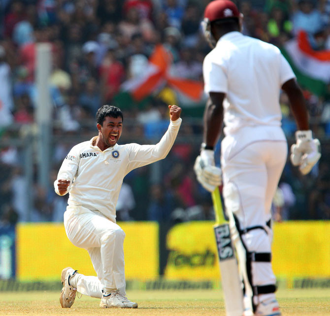 Pragyan Ojha of India celebrates the wicket of Darren Sammy