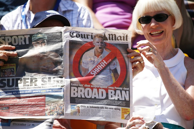 A member of the crowd holds up an anti-Stuart Broad newspaper front page