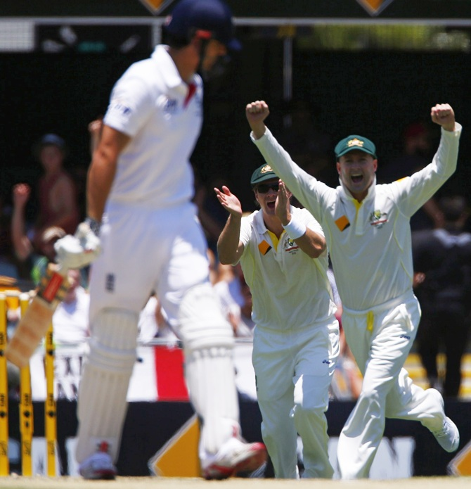 Australia's captain Michael Clarke and team mate Shane Watson celebrate after taking the wicket of England's captain Alastair Cook (left)