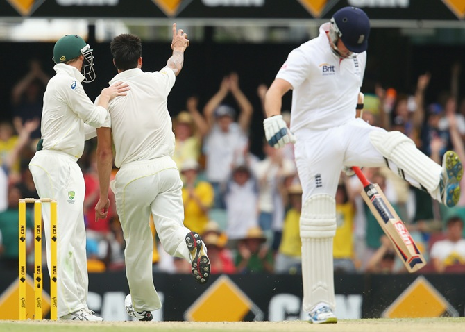 Mitchell Johnson of Australia celebrates taking the wicket of Graeme Swann of England