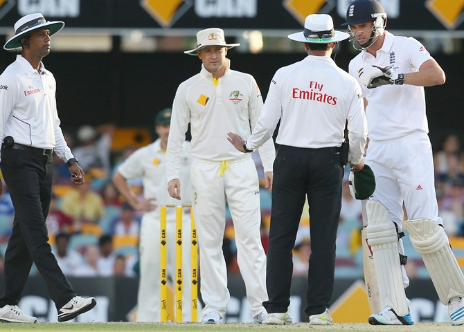 Umpire Kumar Dharmasena and Michael Clarke of Australia look on as Umpire Aleem Dar speaks to James Anderson of England after a verbal altercation