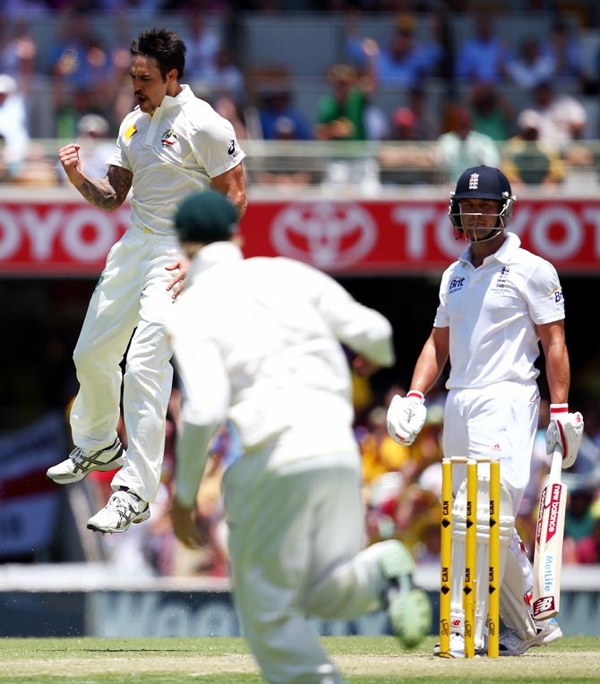 Mitchell Johnson (left) celebrates after taking the wicket of Jonathan Trott (right).