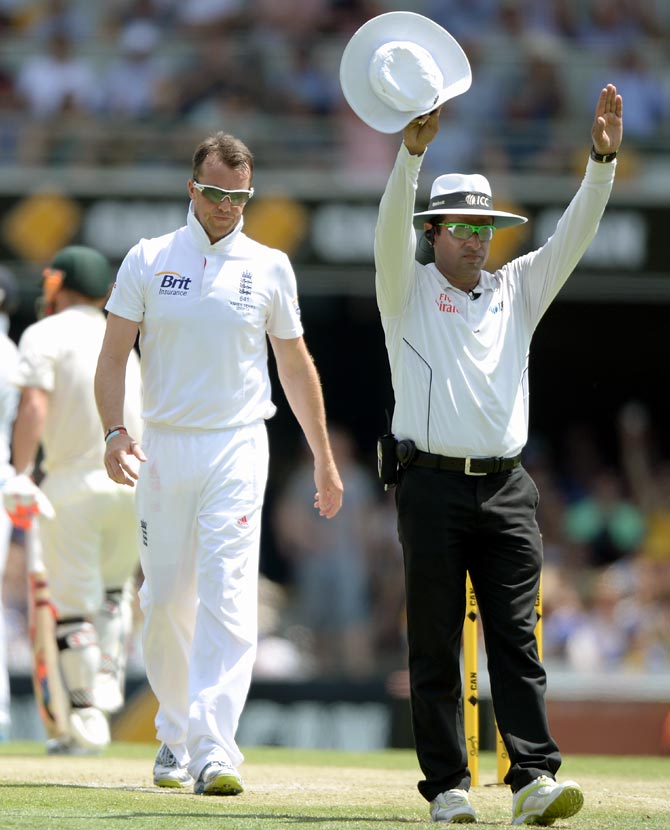 Graeme Swann walks back to his mark after being hit for six by Michael Clarke