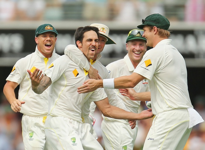 Mitchell Johnson (centre) celebrates a wicket with his team mates