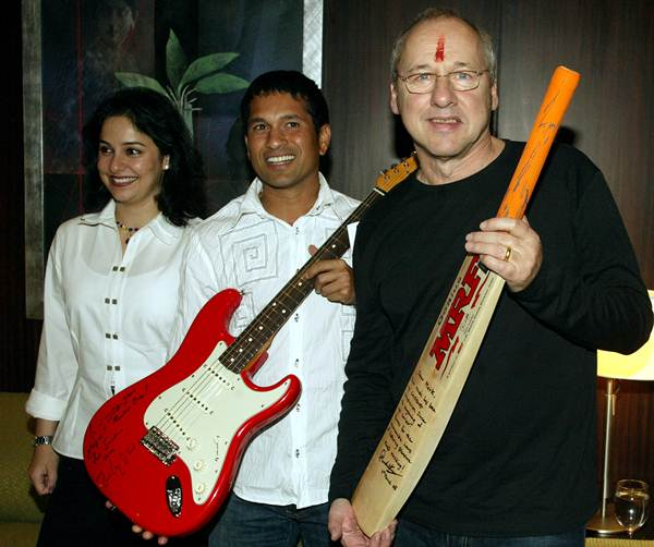 Former Dire Straits lead singer and guitar legend Mark Knopfler with Sachin Tendulkar pose with a bat and guitar, which they gave each other in Bombay on March 4, 2005. Tendulkar's wife Anjali is on the left.