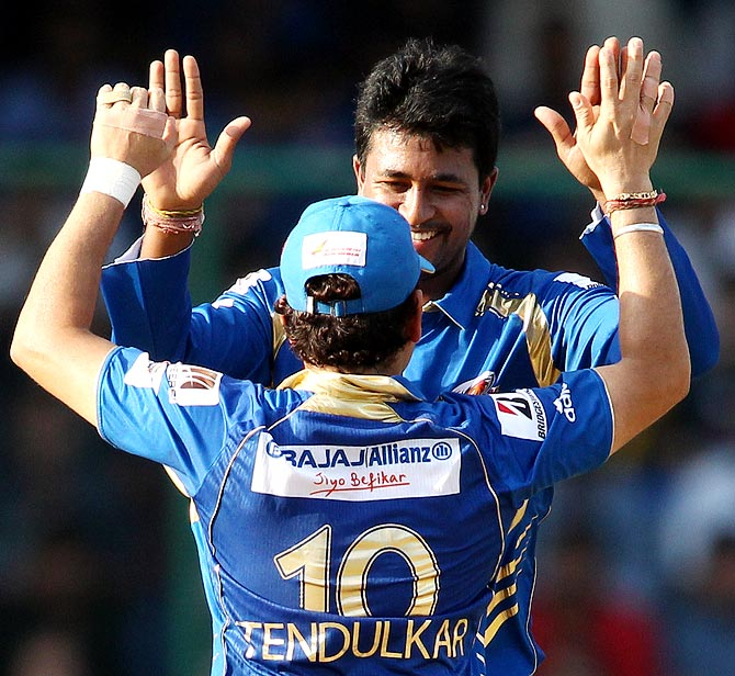 Pragyan Ojha celebrates with Sachin Tendulkar after taking the wicket of Simon Katich