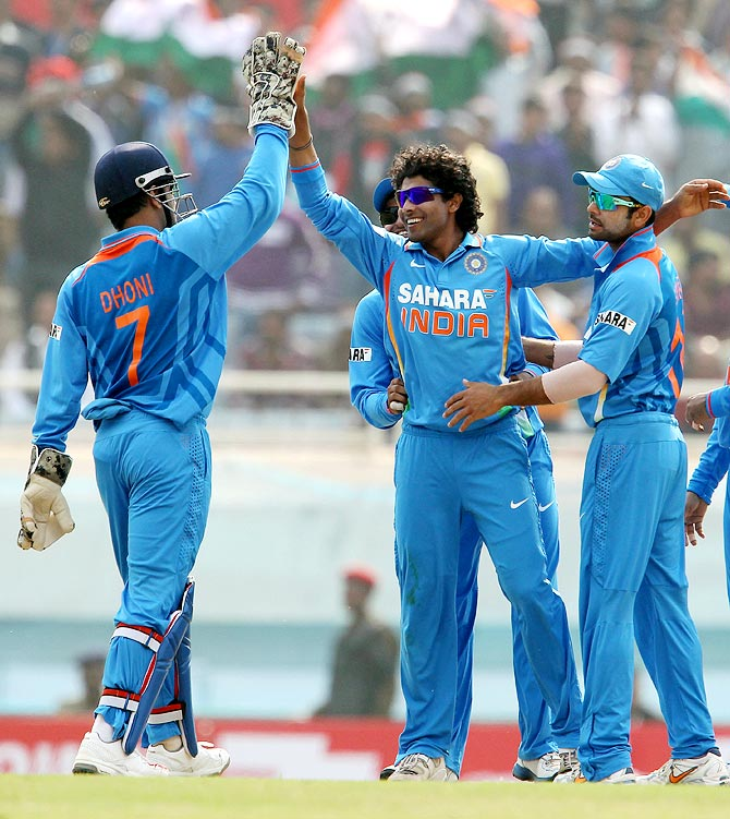 Mahendra Singh Dhoni (left) celebrates with Ravindra Jadeja (centre) and Virat Kohli