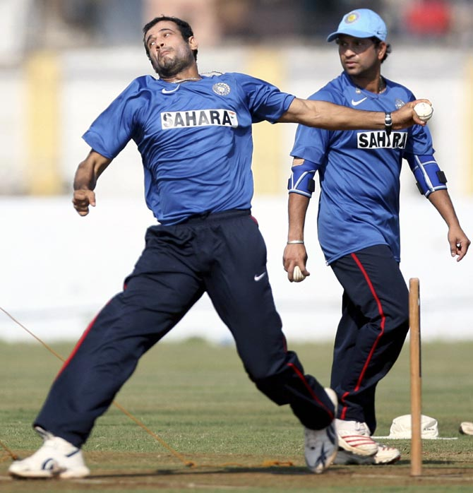 Sachin Tendulkar (right) watches as Irfan Pathan bowls