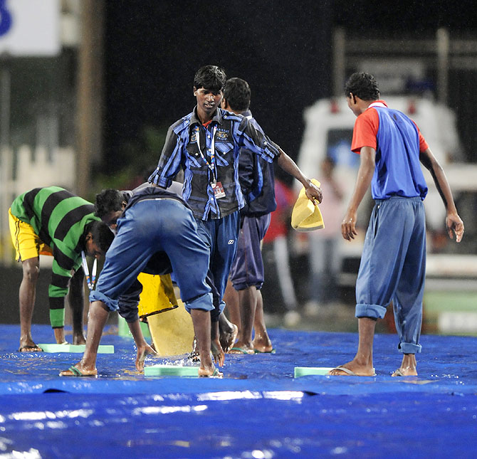 Workers collect water during the 4th ODI in Ranchi, which was abandoned due to rain. The 5th ODI in Cuttack, scheduled for Saturday, is set to face the same fate