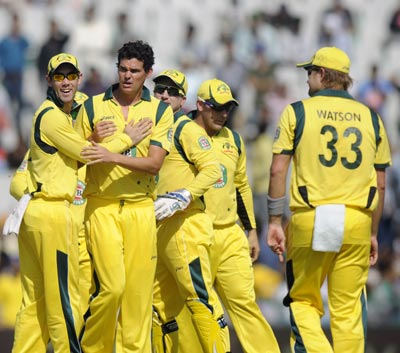 The Australian team celebrates the fall of an Indian wicket