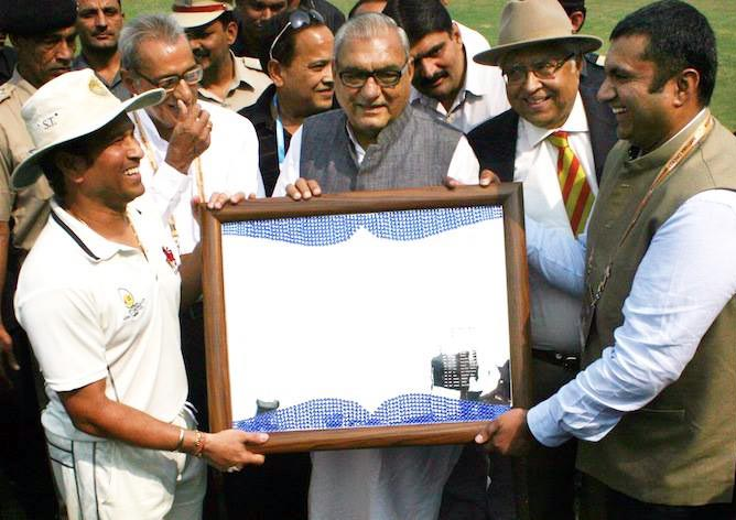 Sachin Tendulkar receives a memento from Haryana chief minister Bhupinder Singh Hooda (centre) and Haryana Cricket Association secretary Anirudh Chaudhary (right)