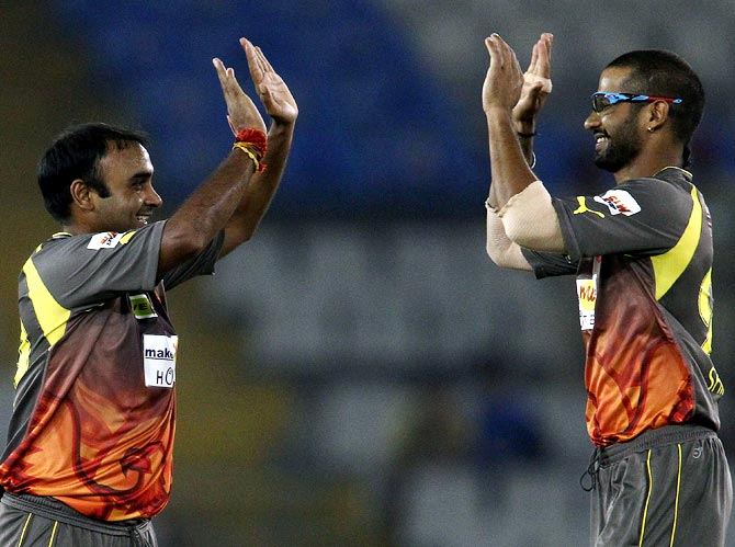 Amit Mishra is congratulated by captain Shikhar Dhawan after taking the wicket of Ali Waqas